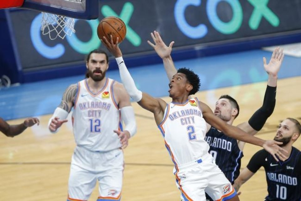 Photo -  Oklahoma City's Shai Gilgeous-Alexander (2) slips past Orlando's Nikola Vucevic  to the basket during a game between the Thunder and the Magic at Chesapeake Energy Arena. Gilgeous-Alexander's mom was a world-class athlete in her own right. [Bryan Terry/The Oklahoman]