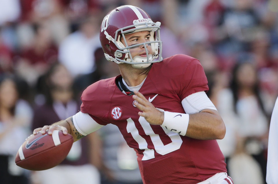 Photo - FILE - In this Sept. 28, 2013 file photo, Alabama quarterback AJ McCarron (10) warms up prior to an NCAA college football game against Mississippi in Tuscaloosa, Ala. McCarron made a pact with himself: He wouldn't go to New York before he's able to pay his own way unless it's for the Heisman Trophy ceremony or the NFL draft. He's headed there this weekend as a Heisman finalist.(AP Photo/Dave Martin, File)