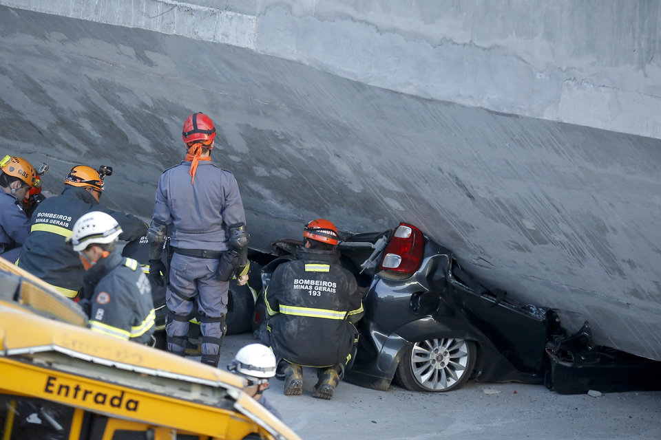 Photo - Fire department personnel work to retrieve a car pressed underneath a collapsed bridge in Belo Horizonte, Brazil, Thursday, July 3, 2014. The overpass under construction collapsed Thursday in the Brazilian World Cup host city. The incident took place on a main avenue, the expansion of which was part of the World Cup infrastructure plan but, like most urban mobility projects related to the Cup, was not finished on time for the event. (AP Photo/Victor R. Caivano)