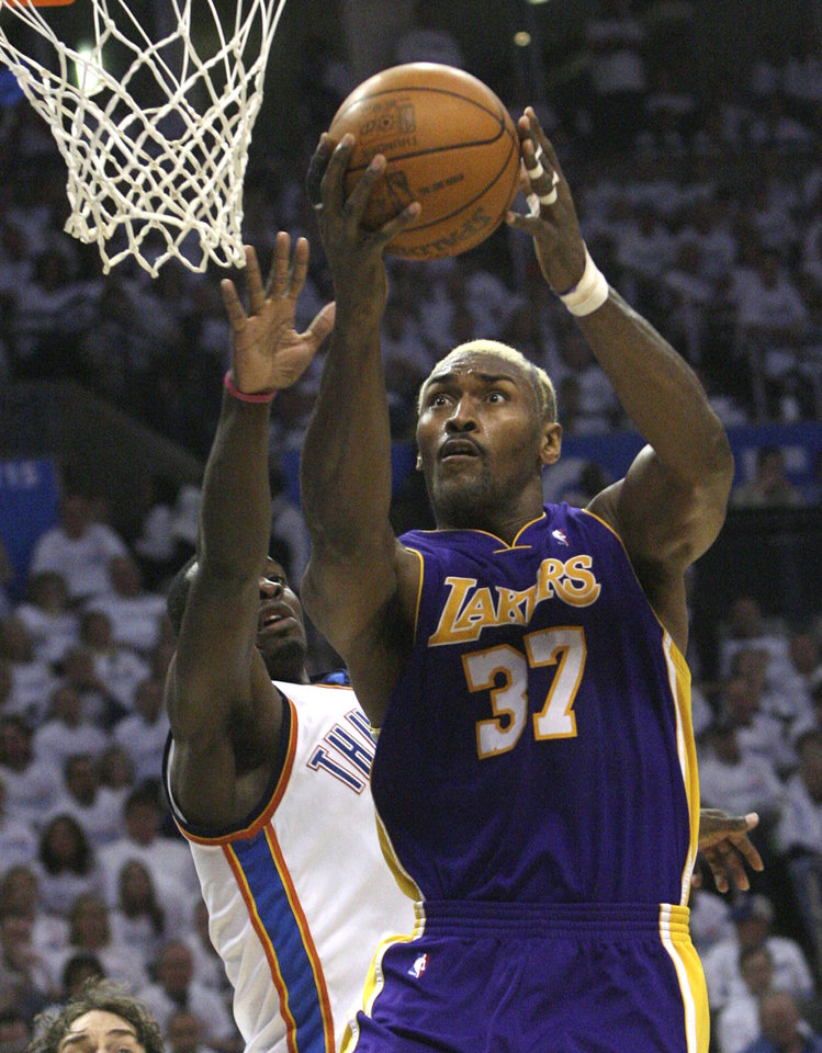 Photo - GAME FOUR / L.A. LAKERS / NBA PLAYOFFS: Los Angeles Lakers forward Ron Artest, right, shoots in front of Oklahoma City Thunder forward Jeff Green, left, in the second quarter of Game 4 of a first-round NBA basketball playoff series, in Oklahoma City, Saturday, April 24, 2010. (AP Photo/Sue Ogrocki) ORG XMIT: OKFC105