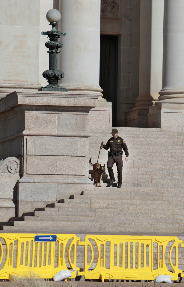 Photo - An Oklahoma Highway Patrol K-9 sniffs around the outside of the state Capitol on Friday after it was evacuated because of a bomb threat. Authorities were investigating a 911 call claiming a bomb would explode at the Governor's Mansion, which resulted in the evacuation at the state Capitol of more than 1,000 people, including more than 500 schoolchildren who were in the building for a special event. Story, Page 11A Photo By David McDaniel, The Oklahoman