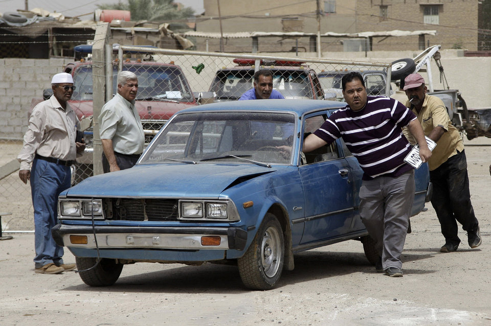 Photo - In this Tuesday, April 10, 2012 photo, a man pushes his old car to be crushed as he holds his car plate at a scrap yard in the southeastern Zafaraniya neighborhood of Baghdad, Iraq. In the Iraqi capital, the bald tires, balky engine and three decades of wear weren't much of a problem. What the buyer really wanted was the old white license plate, a commodity far more valuable than the rusting clunker itself. (AP Photo/Khalid Mohammed) ORG XMIT: BAG506