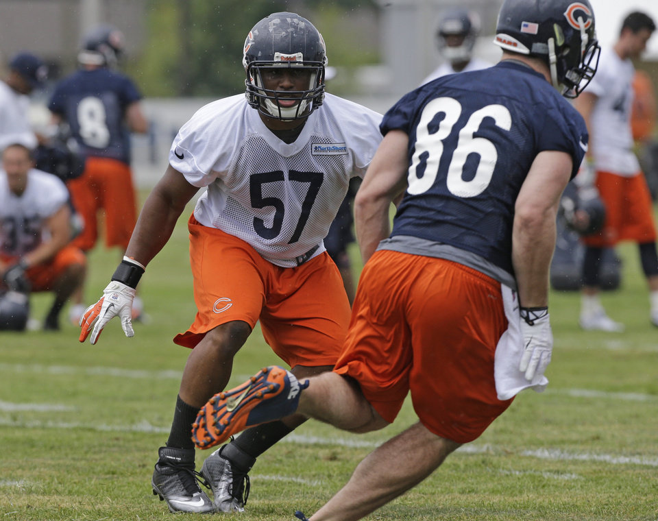 Photo - Chicago Bears linebacker Jonathan Bostic (57) works with teammates during NFL football training camp Friday, July 26, 2013, at Olivet Nazarene University in Bourbonnais, Ill. (AP Photo/Nam Y. Huh)