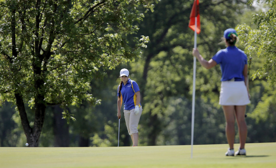 Photo - Katie Goodwin of Riverfield Country Day holds the pin flag as Mikera Morris of Dibble putts during the 2014 Class 2A girls' golf state championship tournament  Wednesday, May 7, 2014, at Trosper Golf Course in Del City.  Photo by Jim Beckel, The Oklahoman