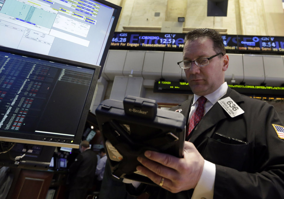 Trader Edward Curran works on the floor of the New York Stock Exchange Thursday, Feb. 28, 2013. Stocks turned mixed Thursday after two days of triple-digit rallies. Big-name companies reported higher quarterly earnings and the government said that the jobless claims are falling, but impending budget cuts cast a pall.  (AP Photo/Richard Drew)