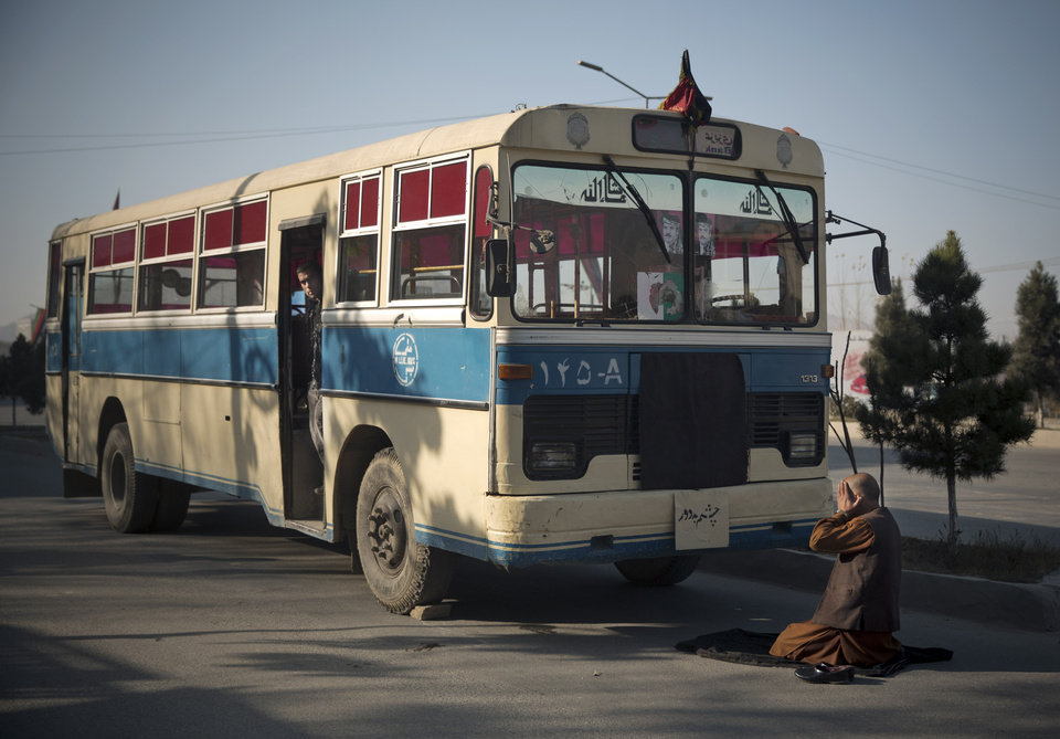 Photo - An Afghan bus driver offers prayers in front of his empty bus, as the center of Kabul came to a still stand, because thousands of prominent Afghans gathered to meet for a Loya Jirga to debate a contentious security agreement with the United States in the Afghan capital, Thursday, Nov. 21, 2013. Afghanistan's president Hamid Karzai said he backs a security deal with the United States but told the gathering of elders that if they and parliament approve the agreement it should be signed after next spring's elections. Without the agreement the United States previously warned that it will remove all its troops by the end of 2014.  (AP Photo/Anja Niedringhaus)