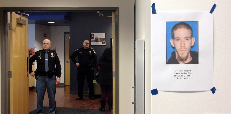 Photo - A photo of Shawn Walter Bair, right, hangs on a wall as Elkhart police wait for the start of a news conference Thursday, Jan. 16, 2014 in Elkhart, Ind. Authorities intified Blair at the man who fatally shot two women in a northern Indiana grocery store on Wednesday. (AP Photo/ Elkhart Truth, Jennifer Shephard) GOSHEN AND MAGAZINES OUT