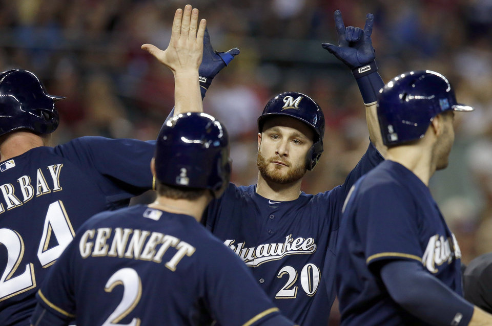 Photo - Milwaukee Brewers' Jonathan Lucroy (20) celebrates with teammates Lyle Overbay, left, Ryan Braun, right, and Scooter Gennett after Lucroy connected for a grand slam against the Arizona Diamondbacks during the seventh inning of a baseball game on Tuesday, June 17, 2014, in Phoenix. (AP Photo/Ross D. Franklin)