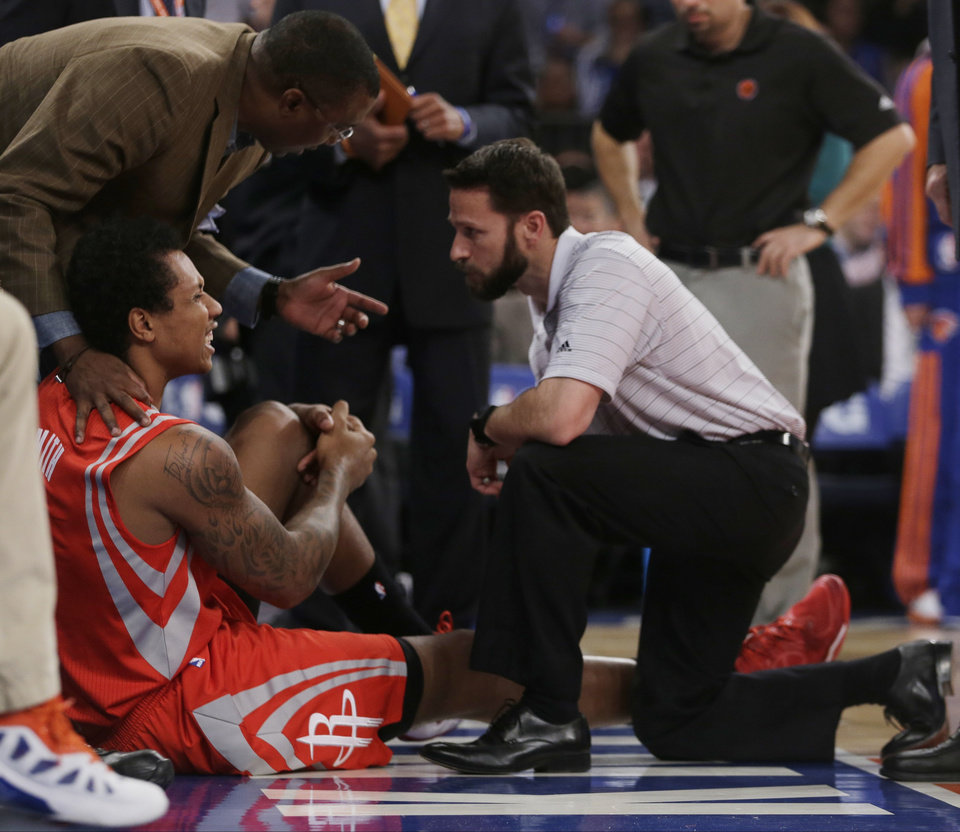 Trainers check on Houston Rockets\' Greg Smith (4) after he was injured during the first half of an NBA basketball game against the New York Knicks on Thursday, Nov. 14, 2013, in New York. (AP Photo/Frank Franklin II)