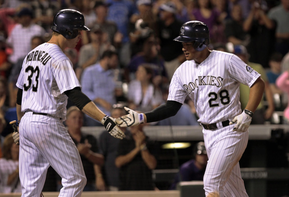 Photo - Colorado Rockies' Justin Morneau (33) congratulates Rockies' Nolan Arenado (28) after Arenado's solo home run in the seventh inning of a baseball game against the Chicago Cubs in Denver on Tuesday, Aug. 5, 2014.(AP Photo/Joe Mahoney)