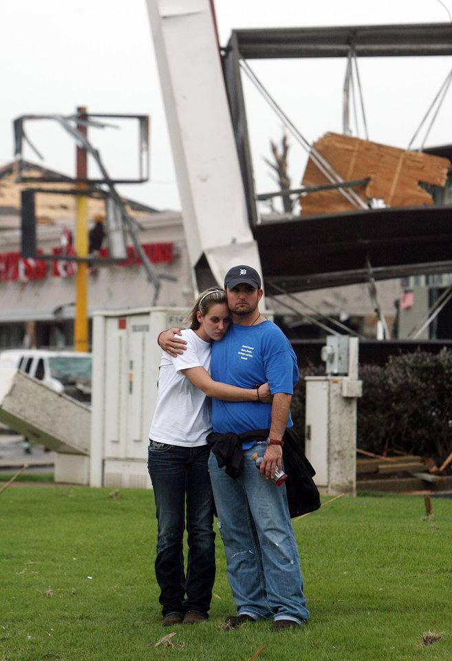Photo - A woman and man hold onto each other at the corner of 15th Street and McFarland Boulevard after a tornado ripped through Tuscaloosa, Ala. Wednesday, April 27, 2011. A wave of severe storms laced with tornadoes strafed the South on Wednesday, killing at least 16 people around the region and splintering buildings across swaths of an Alabama university town. (AP Photo/The Tuscaloosa News, Michelle Lepianka Carter)