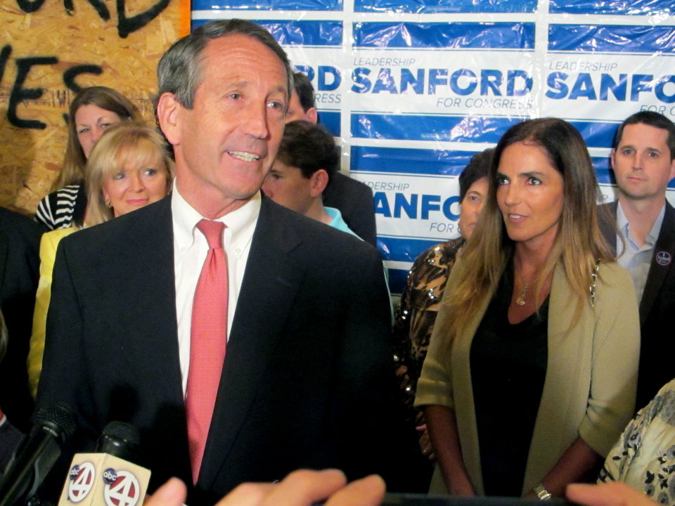 Photo - Former South Carolina Gov. Mark Sanford, with his fiancee Maria Belen Chapur at his side, addresses supporters in Mount Pleasant, S.C., on Tuesday, April 2, 2013, after winning the GOP nomination for the U.S. House seat he once held. Sanford is trying to make a comeback after his political career was derailed four years ago when he disappeared from the state only to return to admit the couple was having an affair. Sanford's wife, Jenny, later divorced him. (AP Photo/Bruce Smith)
