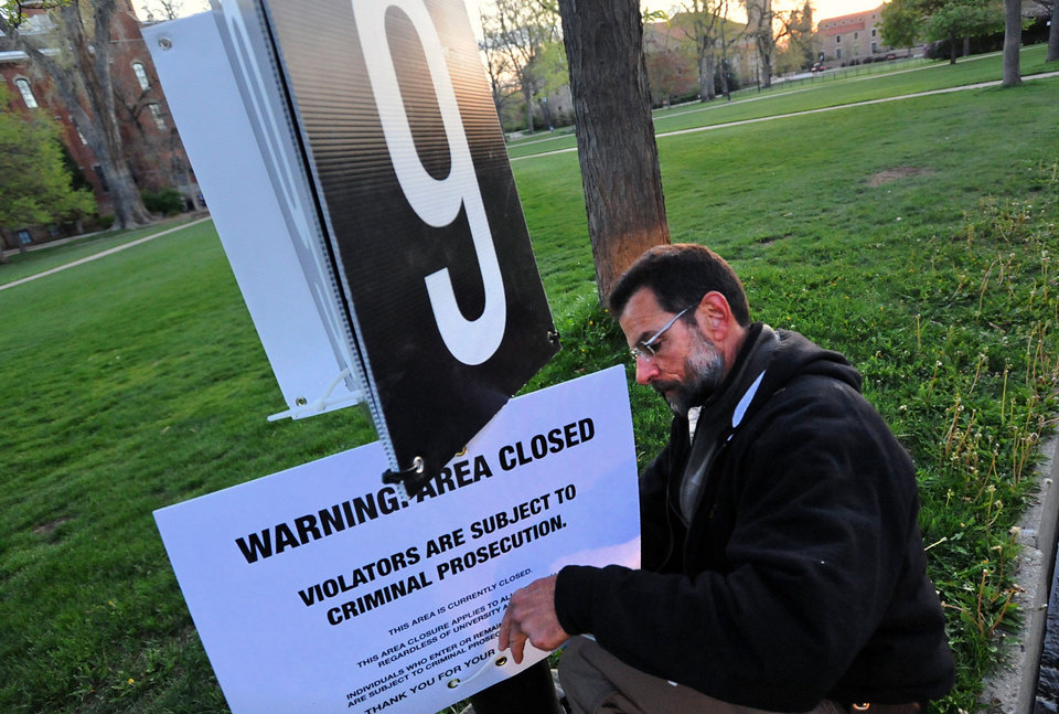 Photo -   A man posts an area closure sign on the Norlin Quad of the University of Colorado Boulder campus on Friday, April 20, 2012. The university is restricting visitors for a day in a bid to stop an annual marijuana protest that last year attracted more than 10,000 people. Every year, many marijuana activists across the nation hold pot-smoking protests on April 20 to demand legalization. The gathering at the University of Colorado in Boulder has become one of the biggest campus protests. (AP Photo/The Daily Camera, Paul Aiken) NO SALES; NO MAGS; NO TV; NO INTERNET