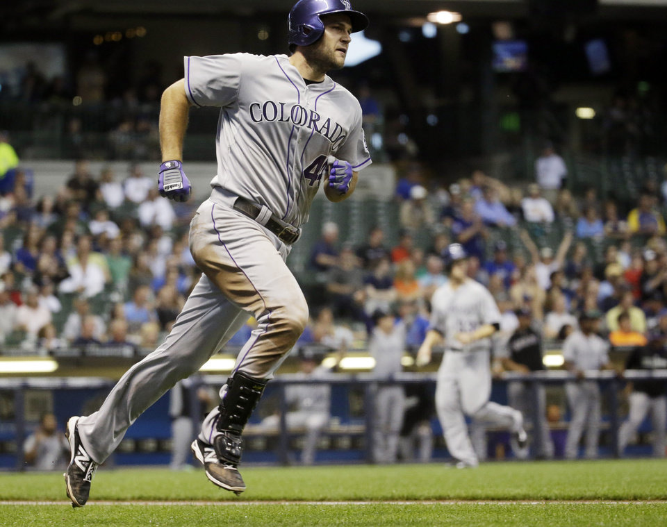Photo - Colorado Rockies' Ryan Wheeler rounds the bases after hitting a grand slam during the fourth inning of a baseball game against the Milwaukee Brewers Thursday, June 26, 2014, in Milwaukee. (AP Photo/Morry Gash)