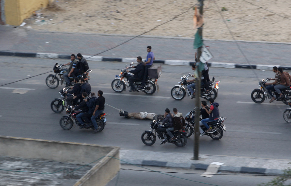 Photo -   Palestinian gunmen ride motorcycles as they drag the body of a man who was killed earlier Tuesday as a suspected collaborator with Israel, in Gaza City, Tuesday, Nov. 20, 2012. The man was one of six suspected collaborators who, according to witnesses, were killed in a main intersection by masked men who forced them to lie down in the street and shot them in the head. The Hamas military wing claimed responsibility. (AP Photo/Hatem Moussa)