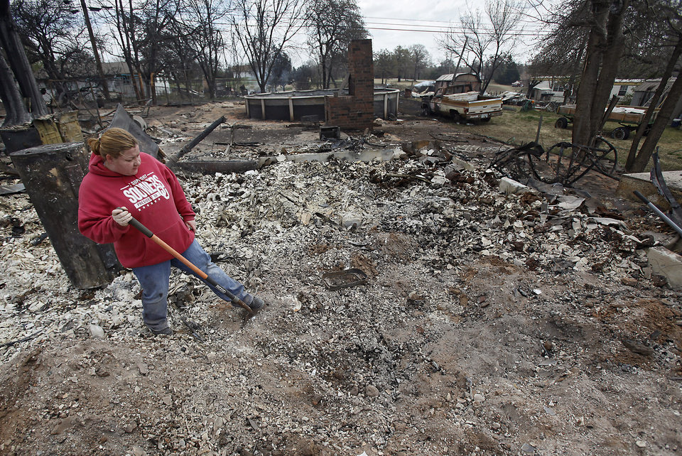 Photo - Terra Brown uses a shovel to dig through the ash as she looks for a fire proof safe in her mother's home that was destroyed by wildfires on Friday, April 10, 2009, in Choctaw, Okla.  Photo by Chris Landsberger, The Oklahoman