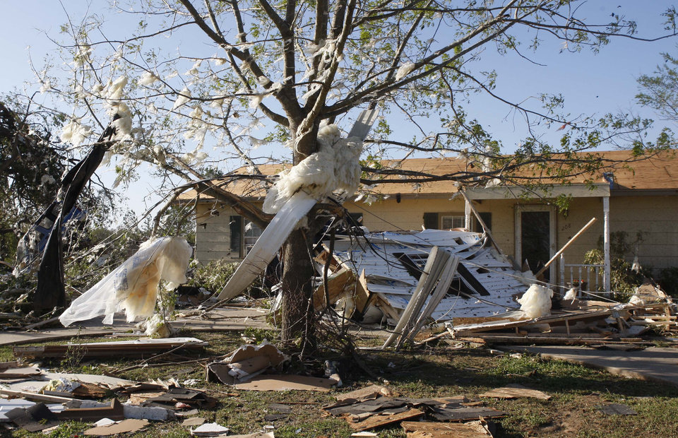 Debris is strewn across a yard in Tushka, Okla., Friday, April 15, 2011, following a tornado the night before. (AP Photo/Sue Ogrocki)