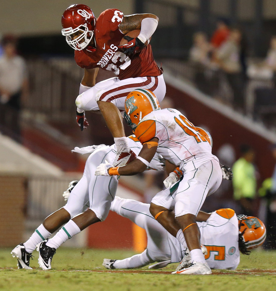 Photo - Oklahoma's Trey Millard (33) leaps past Florida A&M's Jonathan Pillow (19) during the college football game between the University of Oklahoma Sooners (OU) and Florida A&M Rattlers at Gaylord Family—Oklahoma Memorial Stadium in Norman, Okla., Saturday, Sept. 8, 2012. Photo by Bryan Terry, The Oklahoman