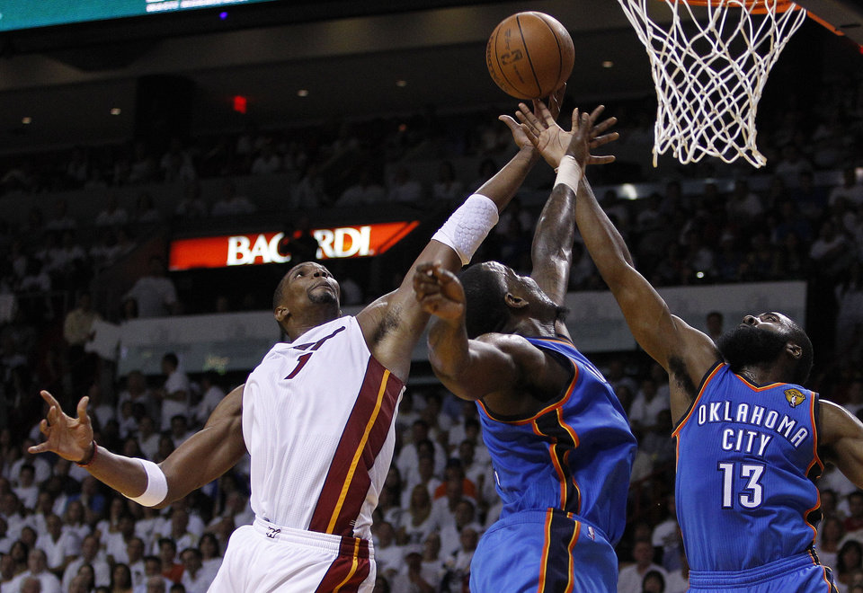 Miami Heat power forward Chris Bosh (1) shoots as Oklahoma City Thunder center Kendrick Perkins (5) and guard James Harden defend during the first half at Game 3 of the NBA Finals basketball series, Sunday, June 17, 2012, in Miami. (AP Photo/Lynne Sladky) ORG XMIT: NBA117