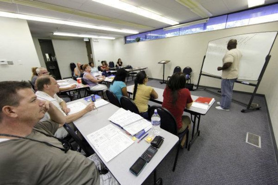 T.L. Tucker teaches a lesson on fractions and decimals during an Oklahoma City GED class at the Adult Learning Center. The loss of state funding will mean fewer classes, instructors and students across the state. Photo by Garett Fisbeck, The Oklahoman <strong>Garett Fisbeck - Garett Fisbeck</strong>