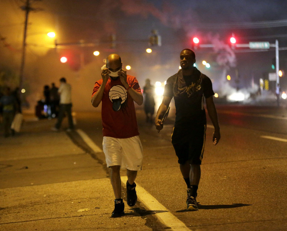 Photo - Men walk away from a cloud of tear gas during a protest Monday, Aug. 18, 2014, for Michael Brown, who was killed by a police officer Aug. 9 in Ferguson, Mo. Brown's shooting has sparked more than a week of protests, riots and looting in the St. Louis suburb. (AP Photo/Charlie Riedel)
