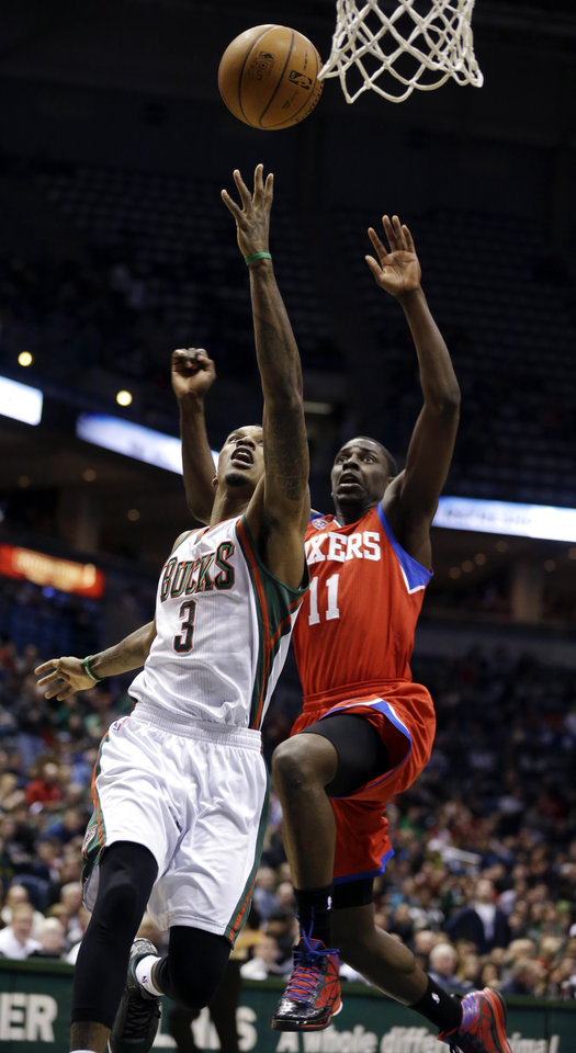 Milwaukee Bucks\' Brandon Jennings (3) drives against Philadelphia 76ers\' Jrue Holiday (11) during the second half of an NBA basketball game, Tuesday, Jan. 22, 2013, in Milwaukee. (AP Photo/Jeffrey Phelps)