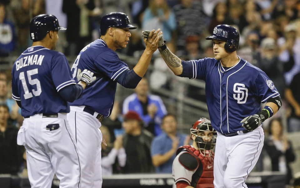 San Diego Padres' Yasmani Grandel celebrates his three run homer against the Arizona Diamondbacks with Jesus Guzman, left, and Kyle Blanks in the Padres' five run fourth inning in a baseball game Saturday, June 15, 2013, in San Diego. (AP Photo/Lenny Ignelzi)