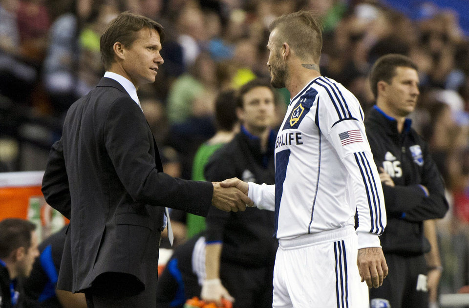 LA Galaxy's David Beckham, right, shakes hands with Montreal Impact coach Jesse Marsch during a break in the first half of an MLS soccer match in Montreal, Saturday, May 12, 2012. (AP Photo/The Canadian Press, Paul Chiasson)
