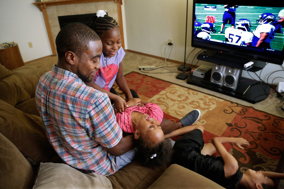 Photo - Adrian Arrington, a former safety at Eastern Illinois University, plays with his children from left, Andria Arrington, Ayana Lucero, and Isaiah Dye, while talking about enduring five concussions while playing, some so severe he has says he couldn't recognize his parents afterward, during an interview with The Associated Press at his home Tuesday, July  29, 2014, in Bloomington Ill.  Subsequent headaches, memory loss, seizures and depression made it difficult to work or even care for his children. The NCAA agreed to settle a class-action head-injury lawsuit by creating a $70 million fund to diagnose thousands of current and former college athletes to determine if they suffered brain trauma playing football, hockey, soccer and other contact sports. Arrington was the lead plaintiff in the lawsuit. (AP Photo/Seth Perlman)