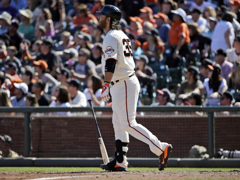 Photo - San Francisco Giants' Brandon Crawford watches the flight of his walk-off home run to beat the Colorado Rockies during the 10th inning of a baseball game on Sunday, April 13, 2014, in San Francisco. The Giants won 5-4. (AP Photo/Marcio Jose Sanchez)