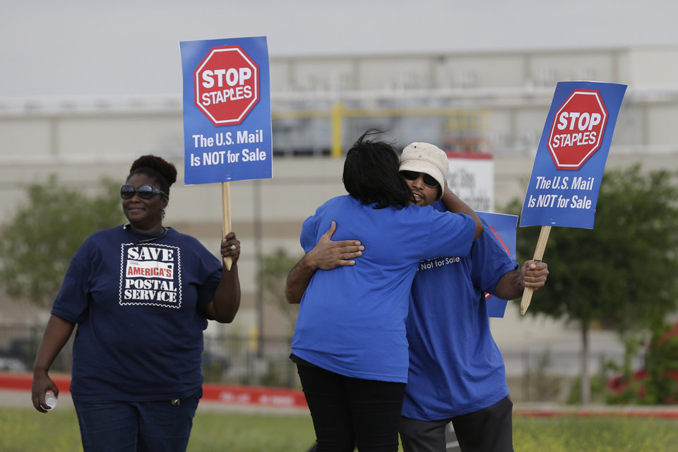 Photo - Postal workers gather to protest in Dallas, Thursday, April 24, 2014.  Thousands of postal workers around the nation are expected to picket outside Staples' stores to protest a pilot program of postal counters in the stores that are staffed with Staples employees. (AP Photo/LM Otero)