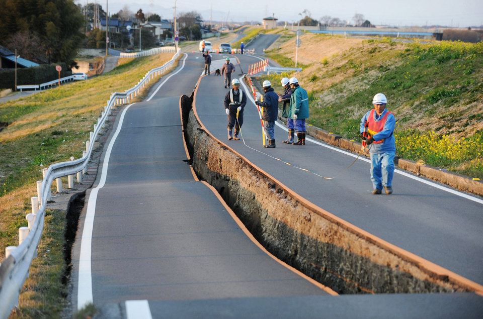 Photo - Workers inspect a caved-in section of a prefectural road in Satte, Saitama Prefecture, after one of the largest earthquakes ever recorded in Japan slammed its eastern coast Friday, March 11, 2011. (AP Photo/Saitama Shimbun via kyodo News) JAPAN OUT, MANDATORY CREDIT, NO SALES, ONLINE OUT, TV OUT ORG XMIT: TOK850