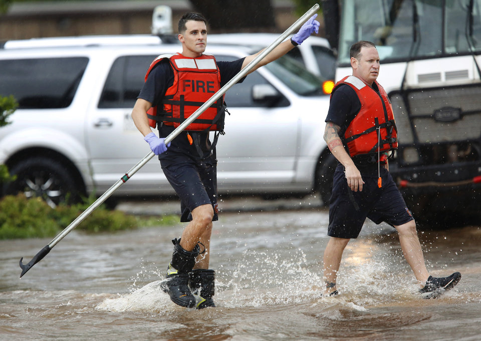 Photo - A firefighter signals a driver to turn to avoid deep water on S. May Avenue after heavy rains overwhelmed stormwater drainage systems and  flooded streets, requiring  high water rescues in Oklahoma City as another round of severe storms passes through the metro. These firefighters are returning to their firetruck after rescuing three people from their vehicles stranded in high water. 