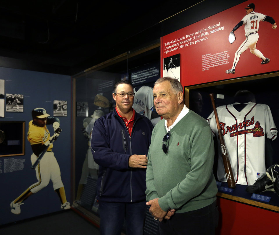 Photo - Former Atlanta Braves pitcher Greg Maddux, left, and former manager Bobby Cox pose by a Braves exhibit during their orientation visit at the Baseball Hall of Fame on Monday, March 24, 2014, in Cooperstown, N.Y. They will be inducted to the hall in July. (AP Photo/Mike Groll)