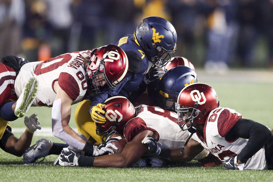 Photo - Oklahoma Sooners tight ends Grant Calcaterra (80) and Brayden Willis (81) recover an onside kick over DWest Virginia Mountaineers safety Josh Norwood (4) during the NCAA football game between the Oklahoma Sooners and the West Virginia Mountaineers at Mountaineer Field at Milan Puskar Stadium in Morgantown, W.Va on Friday, November 23, 2018. IAN MAULE/Tulsa World