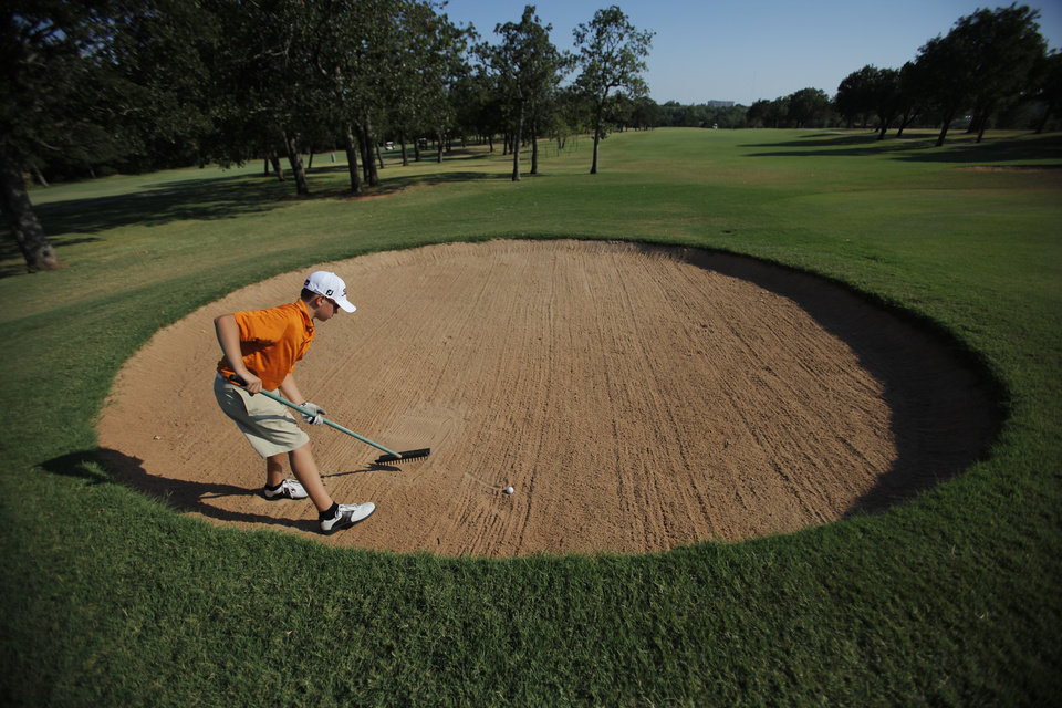 Jack Edmunson, 13, of Luther, retrieves a ball from a sand trap during Family Fun Night at Kickingbird Golf Course, Saturday, June 21, 2012.  Photo by Garett Fisbeck, The Oklahoman