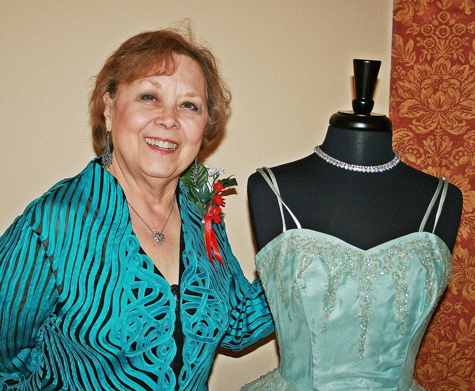 Liz Codding displays her 1957 prom dress. Codding provided seven dresses from her \'Hope Chest\' for a \'senior\' prom held recently at Touchmark at Coffee Creek. Cheyenne Middle School students helped with the prom.