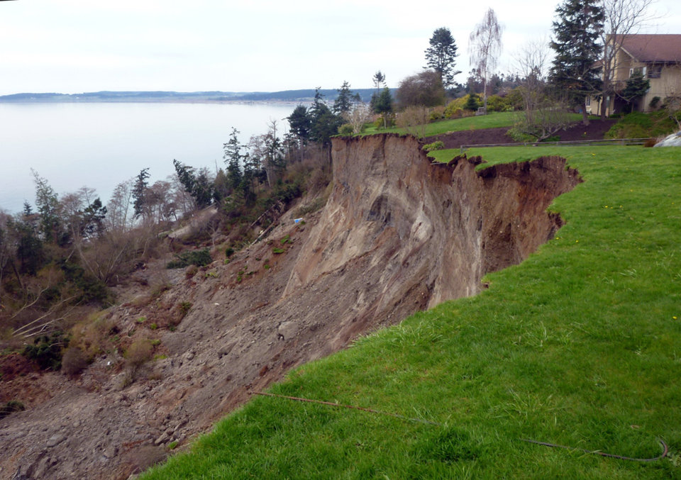 Photo - This March 27, 2013 photo provided by the Washington Dept. of Natural Resources, shows a home near the edge of a massive landslide that damaged one home and isolated or threatened more than 30 others near Coupeville, Wash.  Geologists and engineers are assessing what might happen next after a large landside thundered down the scenic island hillside overlooking Puget Sound. (AP Photo/Washington Dept. of Natural Resources, Stephen Slaughter)
