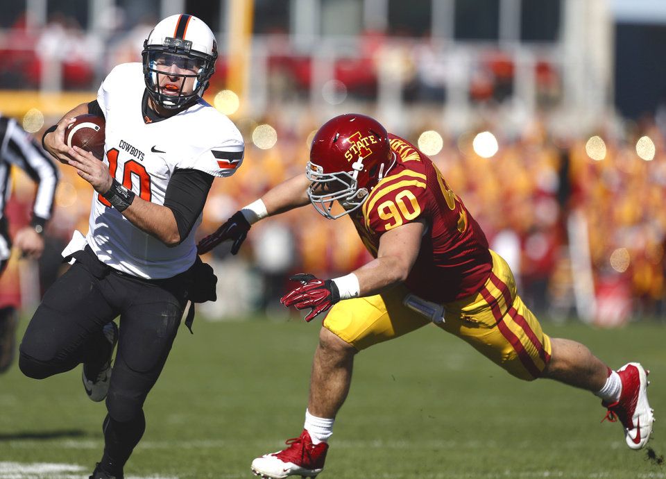 Oklahoma State�s Clint Chelf, left, tries to get by Iowa State�s Mitchell Meyers during Saturday�s game in Ames, Iowa. Chelf had nine carries for 85 yards but completed only 10 of 26 passes and had one interception. Photo by Sarah Phipps, The Oklahoman