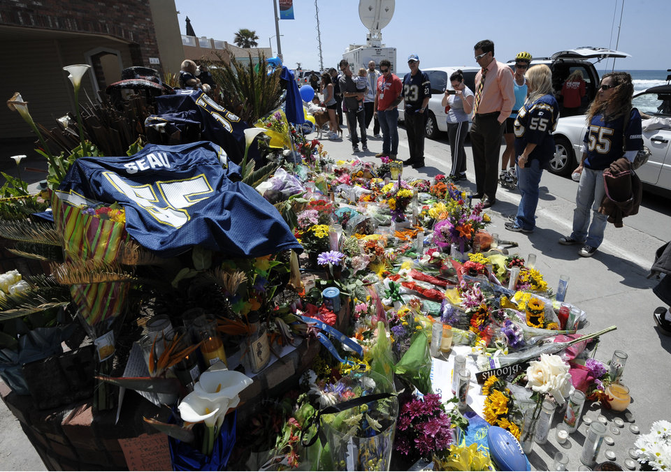 Photo -   A San Diego Chargers #55 jersey sits in the foreground as fans look over a memorial in driveway of former NFL star Junior Seau's house, Thursday, May 3, 2012, in Oceanside, Calif. Seau's death in Oceanside, in northern San Diego County, stunned the region he represented with almost reckless abandon. (AP Photo/Denis Poroy)