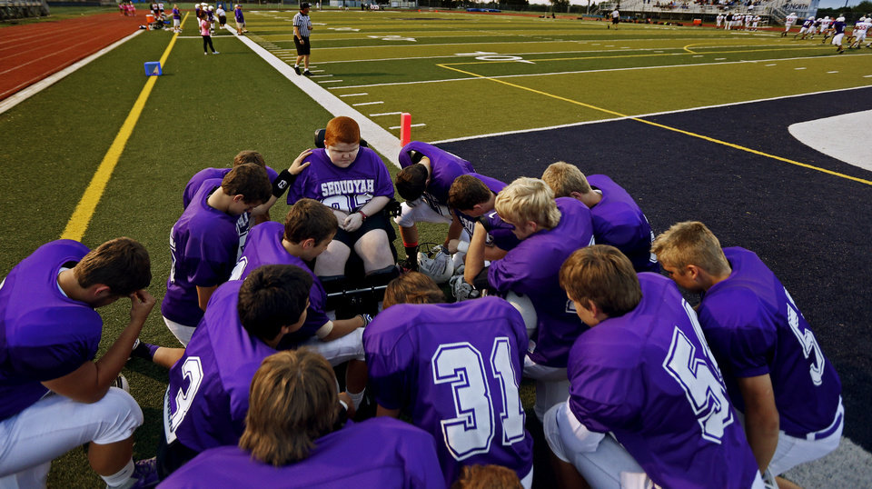 Photo - Keegan Erbst prays with the team before a Sequoyah Middle School football game, Thursday, September 27, 2012. Keegan, who has muscular dystrophy and is confined to a wheelchair, got involved with the team after players Lucas Coker, James Colton, and Parker Tomlinson, pushed suggested it to the coach.  Photo by Bryan Terry, The Oklahoman