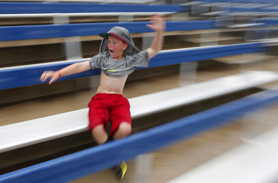 Camden Holt slides across the wet stadium seats as it began to rain in the Class 4A Oklahoma State High School Slow Pitch Softball Championship at ASA Hall of Fame Stadium in Oklahoma City, Wednesday, May 1, 2013. Photo by Chris Landsberger, The Oklahoman