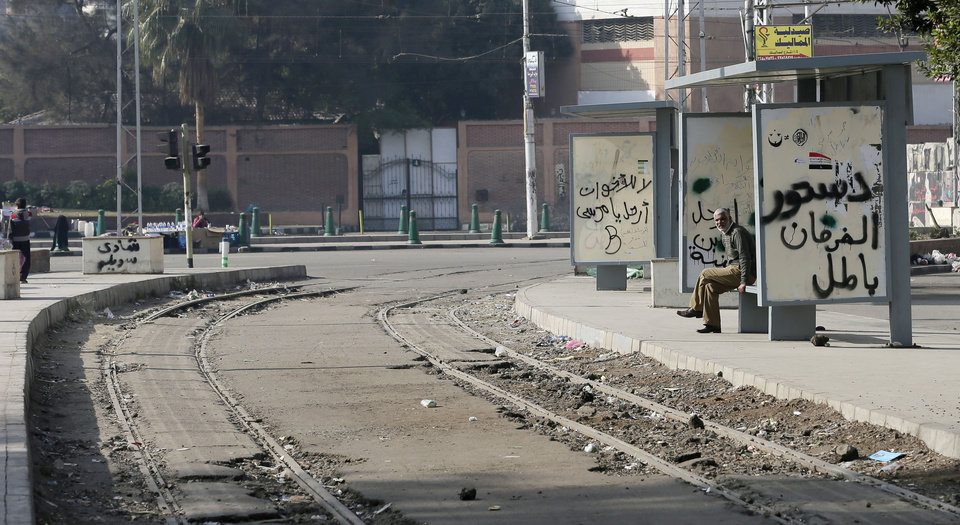 "A man sits on a bench in front of the presidential palace in Cairo, Egypt, Thursday, Dec. 13, 2012. Egypt's opposition called on its followers to vote ""no"" in a crucial referendum on a disputed constitution drafted by Islamist supporters of President Mohammed Morsi. (AP Photo/Hassan Ammar)"