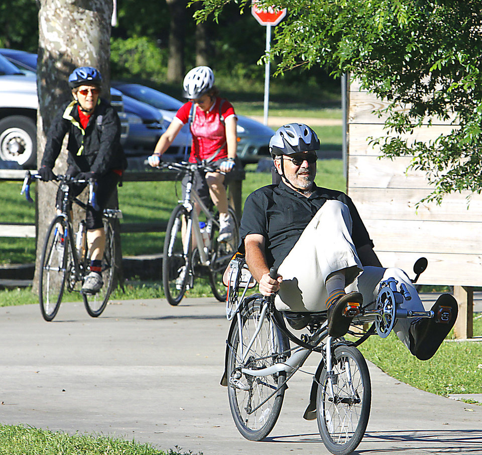 Photo - Paul Minnis arrives on his recumbent bicycle to the Bike to Work Day rally Friday at Andrews Park in  Norman. Photo by Steve Sisney, The Oklahoman
