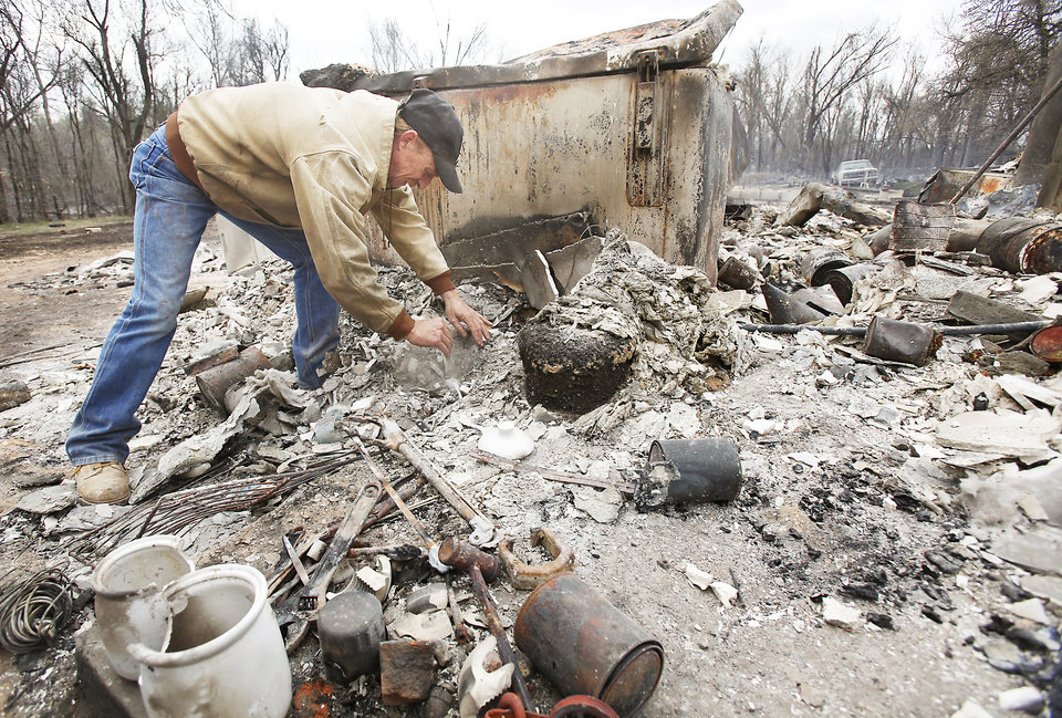 Photo - Kenneth Wertz searches the debris of his family's house Friday at 1480 S Anderson Road. The house and  nearby barn were destroyed in Thursday's wildfire. PHOTO BY CHRIS LANDSBERGER, THE OKLAHOMAN