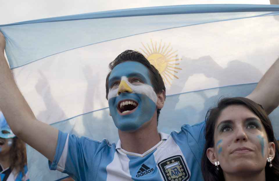 Photo - Soccer fans of the Argentina national soccer team cheer during a live telecast of the soccer World Cup semifinal match between Argentina and The Netherlands, inside the FIFA Fan Fest area on Copacabana beach, in Rio de Janeiro, Brazil, Wednesday, July 9, 2014. (AP Photo/Silvia Izquierdo)