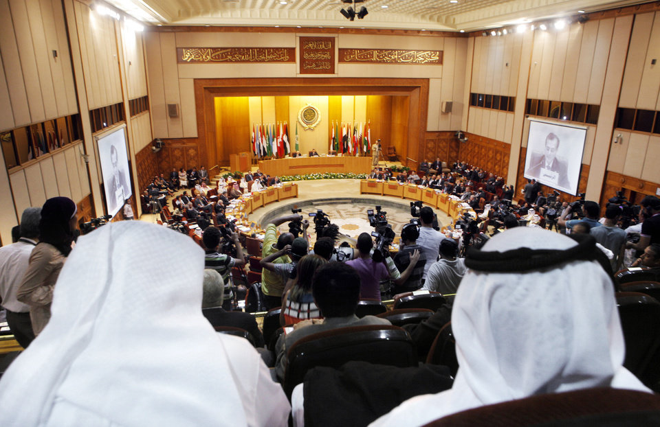Photo -   Arab delegations attend the Arab League's ministerial council meeting at the League's headquarters in Cairo, Egypt, Wednesday, Sept. 5, 2012. Egyptian President Mohammed Morsi made remarks at the opening session which began early Wednesday at the Arab League headquarters. Morsi promised that all Syrian students in Egypt will be treated the same as Egyptians rather than foreigners. Lebanese foreign affairs minister Adnan Mansour and the chairman of the session is seen on both screens. (AP Photo/Amr Nabil)