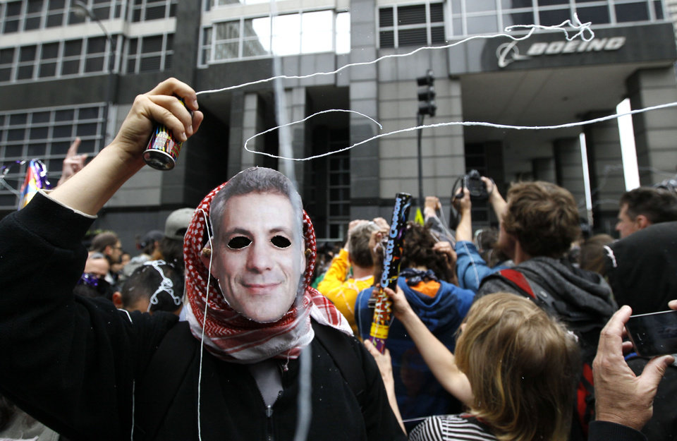 Photo -   A protester wearing mask of Chicago Mayor Rahm Emanuel, shoots out silly string during a demonstration outside Boeing corporate offices Monday, May 21 2012, in Chicago, on the final day of the NATO summit. (AP Photo/Charles Rex Arbogast)