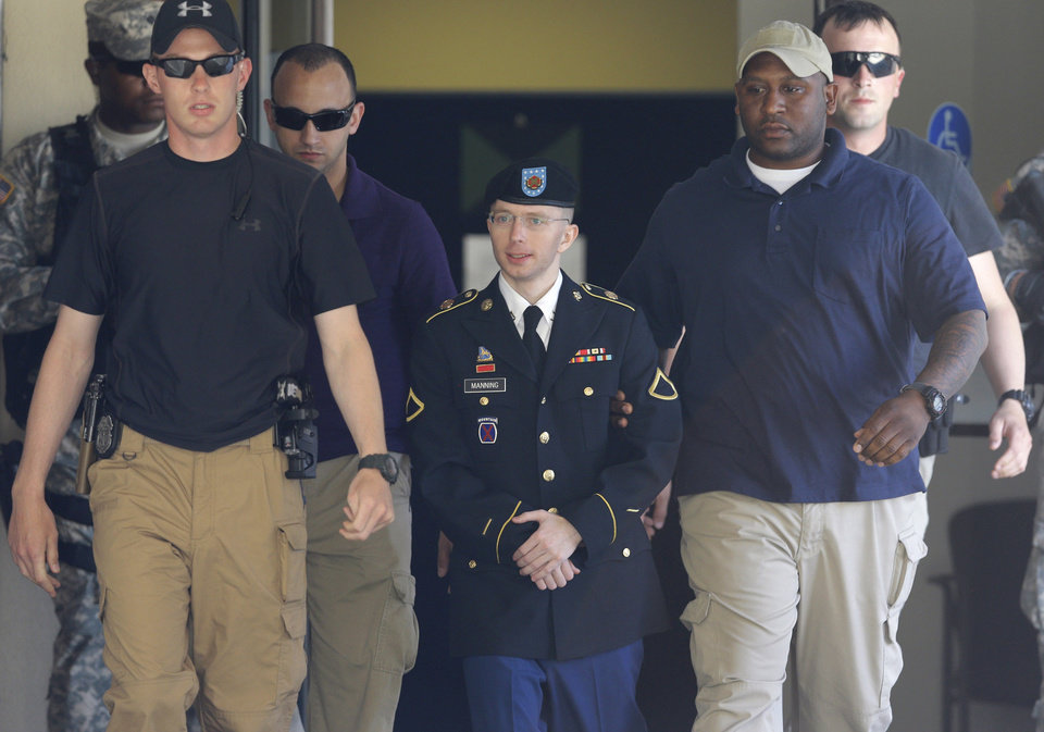Photo - Army Pfc. Bradley Manning, center, is escorted out of a courthouse in Fort Meade, Md., Tuesday, June 4, 2013, after the second day of his court martial. Manning is charged with indirectly aiding the enemy by sending troves of classified material to WikiLeaks. He faces up to life in prison. (AP Photo/Patrick Semansky)