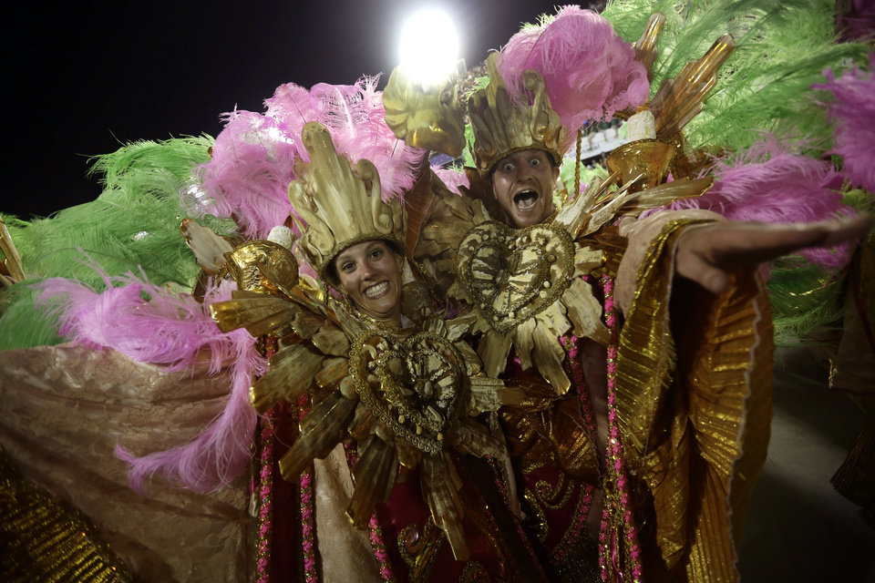 U.S. citizen Paul Leaury, right, and an unidentified fellow foreign member of the Mangueira samba school, dance during a carnival parade at the Sambadrome in Rio de Janeiro, Brazil, Tuesday, Feb. 12, 2013. While non-Brazilians have long shelled out hundreds of dollars for the right to dress up in over-the-top costumes and boogie in Rio\'s samba school parades, which wrapped up Monday in an all-night extravaganza, few in the so-called